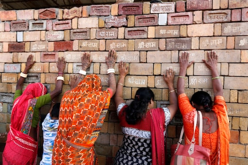"""In this November 11, 2019 file photo, women pray to the bricks reading """"Shree Ram"""", which are expected to be used in constructing Ram temple, in Ayodhya. (AP Photo/Rajesh Kumar Singh, File)"""