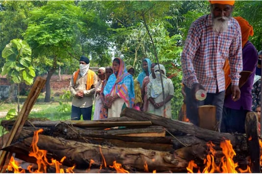 People gather for the cremation of a man who allegedly died after consuming hooch. (PTI)