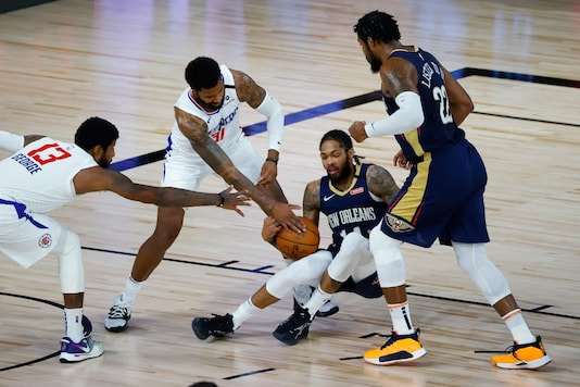 New Orleans Pelicans' Brandon Ingram goes down as Los Angeles Clippers' Marcus Morris Sr. (31) and Paul George (13) go for the ball during an NBA basketball game Saturday, Aug. 1, 2020, in Lake Buena Vista, Fla. (Kevin C. Cox/Pool Photo via AP)