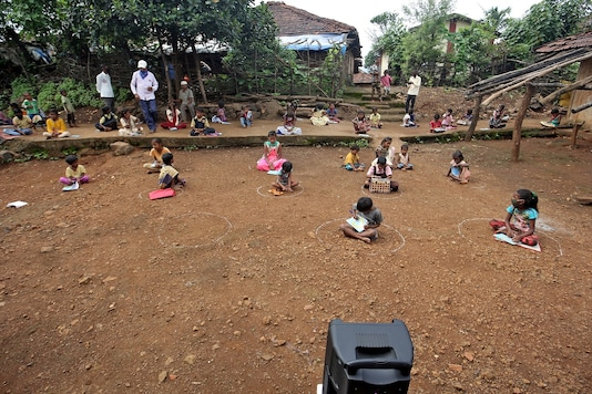Children, who have missed their online classes due to a lack of internet facilities, sit on the ground in circles drawn with chalk to maintain safe distance as they listen to pre-recorded lessons over loudspeakers, after schools were closed following the coronavirus disease (COVID-19) outbreak, in Dandwal village in the western state of Maharashtra,  July 23, 2020. REUTERS/Prashant Waydande