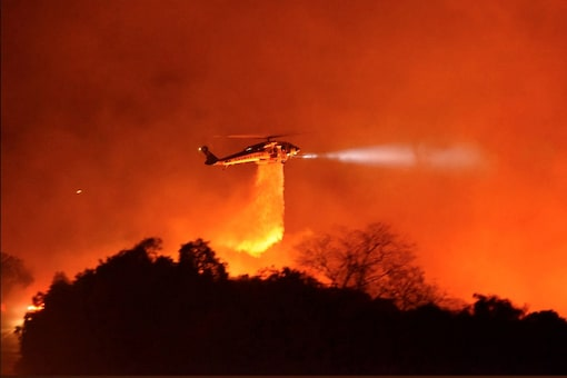 A Los Angeles County Firehawk helicopter makes a water drop on flames during the Cave fire in Los Padres National Forest near East Camino Cielo, Santa Barbara, California, U.S. November 25, 2019,  in this picture obtained from social media. Mandatory credit Mike Eliason/Santa Barbara County Fire Department/via REUTERS