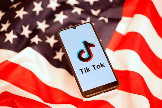 The logo of the much-controversial TikTok app is seen on a smartphone, against the backdrop of the national flag of the United States of America. (Image: Reuters)