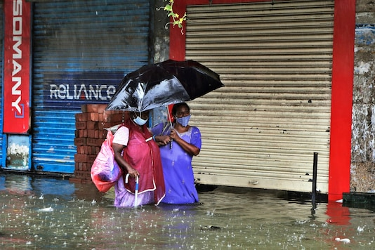 (Image for representation) People wearing masks as a precaution against the coronavirus try to make their way through a water logged street. (AP Photo/Rajanish Kakade)