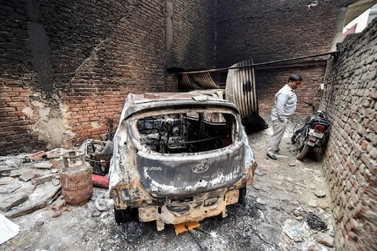 File photo of the charred remains of vehicles set ablaze by rioters during communal violence over the amended citizenship law at Shiv Vihar area of the riot-affected northeast Delhi. (Image: PTI)