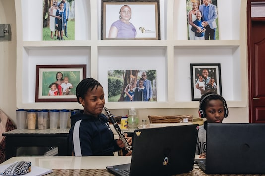 Verisiah Kambale, 11, who has continued her private school's classes via online, and her younger brother Joseph Tayo Kambale use laptops at their home in Nairobi, Kenya, on July 30, 2020. (Khadija Farah/The New York Times)