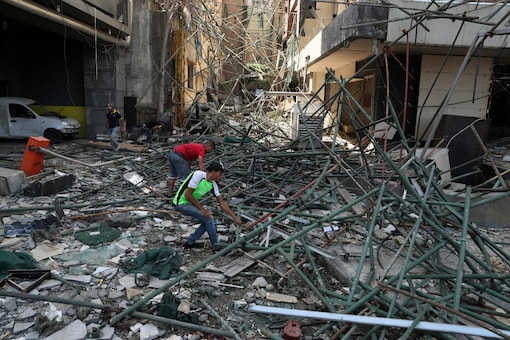 Workers remove rubble from damaged buildings near the site of an explosion on Tuesday that hit the seaport of Beirut, Lebanon, on August 6, 2020. (AP Photo/Bilal Hussein)