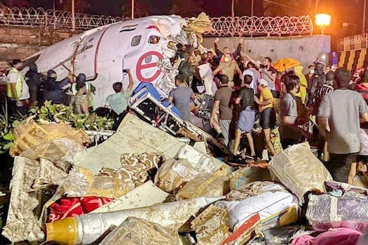 Rescue workers at the site of the crash in Kozhikode on Friday. (PTI)