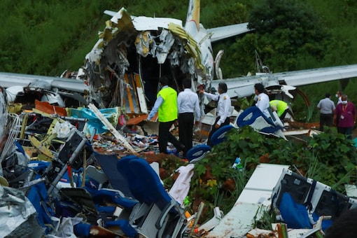 Officials inspect the wreckage of an Air India Express jet at Calicut International Airport in Karipur, Kerala, on August 8, 2020. (AFP)