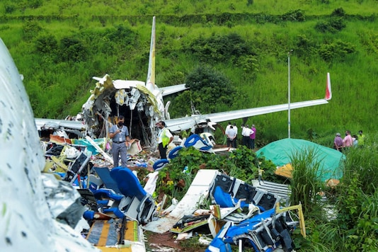 Officials inspect the wreckage of an Air India Express jet at Calicut International Airport in Karipur, Kerala, on August 8, 2020. (Arunchandra Bose/AFP)