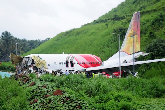 Officials stand on the debris of the Air India Express flight that skidded off a runway in Kozhikode, on Saturday. (AP)