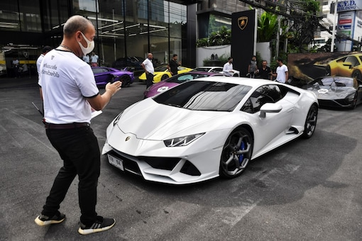This photo taken on July 31, 2020 shows employees helping Lamborghini car owners park during a Lamborghini Club Thailand event at a showroom in Bangkok. With tourism and exports in freefall, Thailand's growth could shrivel by as much as 10 percent this year, dumping millions into unemployment. But in a split-screen economy there are plenty with immunity to the economic scourge caused by COVID-19. (AFP)