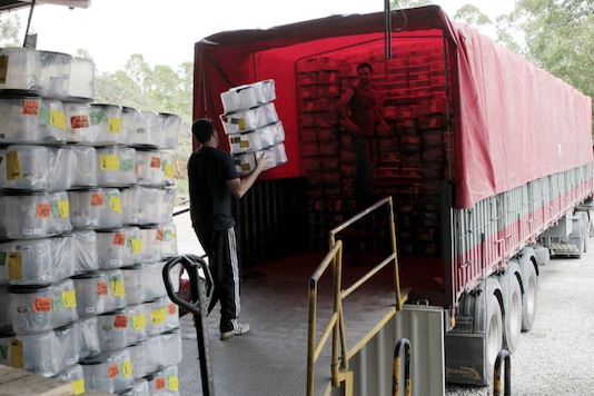 In this representational photo, a man loads plastic boxes into a truck. (Reuters/File)