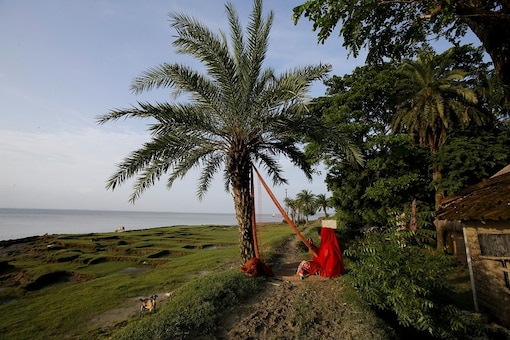 Mahabuba Khatun, 15, cleans a fishing net in front of her house on Ghoramara Island, West Bengal. (Reuters)