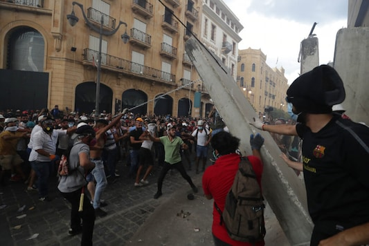 Protesters remove a concrete slab from a barrier to open a road leading to the parliament building during anti-government protests following Tuesday's massive explosion which devastated Beirut, Lebanon, Monday, Aug. 10, 2020. (AP Photo/Hassan Ammar)