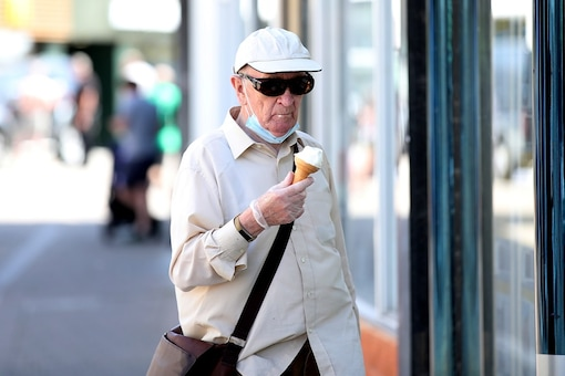 A man wearing a protective face mask and gloves eats an ice cream in Loughborough, following the outbreak of the coronavirus disease (COVID-19), Loughborough, Britain.  (Reuters)