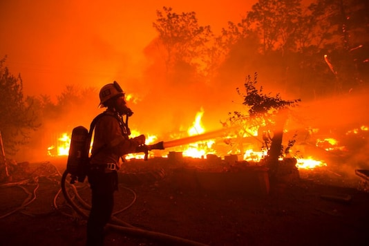 A firefighter works against the Lake Hughes fire in Angeles National Forest on Wednesday, Aug. 12, 2020, north of Santa Clarita, Calif. (AP Photo/Ringo H.W. Chiu)