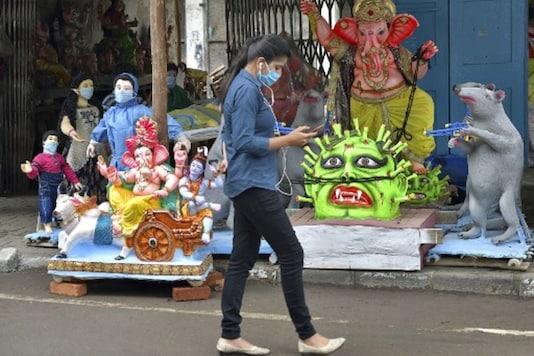 A woman walks past idols depicting the current pandemic scenario in Bengaluru. (AFP)
