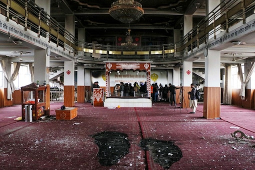 Security personnel inspect a damaged Sikh temple alongside media representatives following a gun attack in Kabul on March 25, 2020. (Photo by STR / AFP)