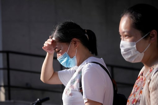 FILE PHOTO: Women wearing masks are seen on a hot summer day, amid the coronavirus disease (COVID-19) pandemic, in Shanghai, China August 14, 2020. REUTERS/Aly Song/File photo