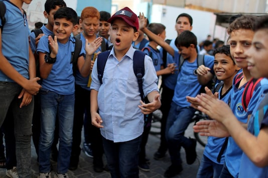 Abdel-Rahman Al-Shantti, an 11-year-old Gaza rapper, is surrounded by students as he performs in his school in Gaza City August 16, 2020. REUTERS/Mohammed Salem