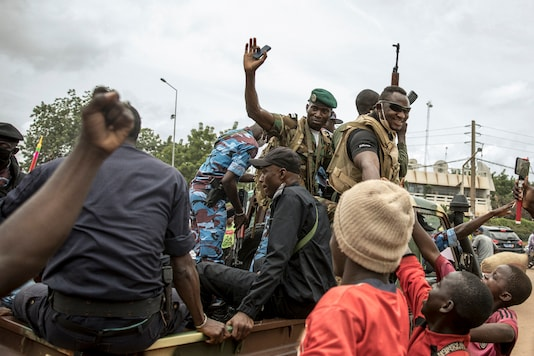 People cheer in celebration as security forces drive through the streets of the capital Bamako, Mali, Wednesday, Aug. 19, 2020, a day after armed soldiers fired into the air outside President Ibrahim Boubacar Keita's home and took him into their custody. (AP Photo)