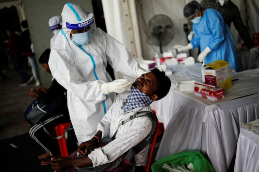 A healthcare worker wearing personal protective equipment (PPE) takes a swab from a migrant worker, who returned to Delhi from his native state, for a rapid antigen test at a bus terminal, amidst the coronavirus disease (COVID-19) outbreak. REUTERS/Adnan Abidi