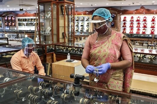 FILE PHOTO: A sales woman wearing a face shield and a mask arranges gold bangles at a jewelry showroom in Kolkata, India, May 26, 2020. REUTERS/Rupak De Chowdhuri
