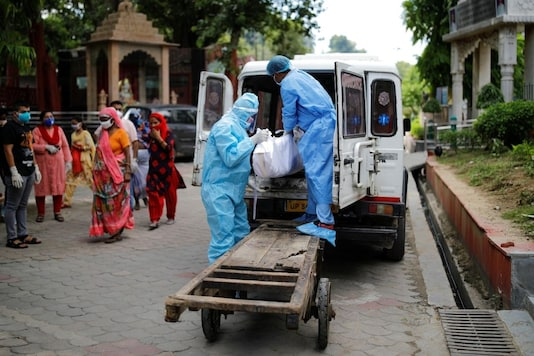 Workers wearing personal protective equipment (PPE) unload a body of a man who died due to the coronavirus disease (COVID-19) before his cremation at a crematorium in New Delhi, India August 22, 2020. REUTERS/Adnan Abidi