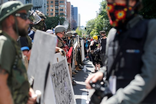 Opposing rallies battle with mace, paint balls and rocks near Justice Center in downtown Portland Saturday, August 22, 2020. (Brooke Herbert/The Oregonian via AP)