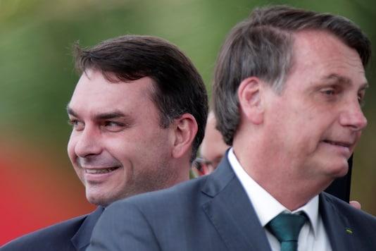 Brazil's Senator Flavio Bolsonaro smiles near Brazil's President Jair Bolsonaro after the launch of a new political party, the Alliance for Brazil (APB) in Brasilia, Brazil. (Reuters)