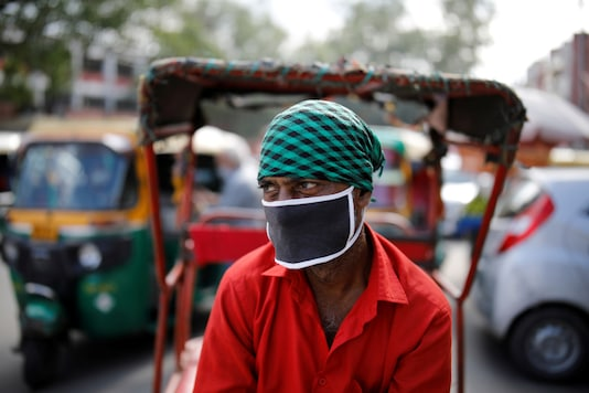 A rickshaw puller wearing a protective face mask waits for customers on a street, amidst the spread of coronavirus disease (COVID-19), in the old quarters of Delhi, India, August 24, 2020. REUTERS/Adnan Abidi