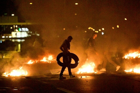 Demonstrators burn tyres during a riot in the Rosengard neighbourhood of Malmo, Sweden August 28, 2020. TT News Agency via REUTERS