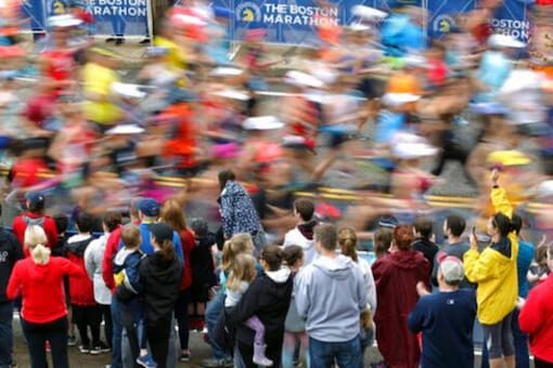 Fans cheer on the third wave of runners at the start of the 123rd Boston Marathon in Hopkinton, Mass. Credits: AP