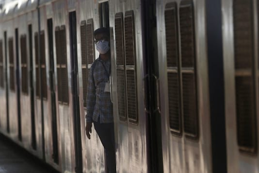 A person wearing a mask standing on the gate of a local train in Mumbai. (File photo/AP)