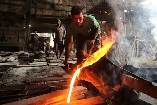 A worker pours molten iron from a ladle to make automobile spare parts inside an iron casting factory in Ahmedabad. (REUTERS/Amit Dave)
