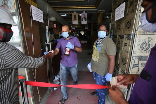 Salespersons handover liquor bottles to customers at the entrance of their outlet during a lockdown to curb the spread of new coronavirus, in Bangalore, on May 6, 2020. (AP Photo/Aijaz Rahi)