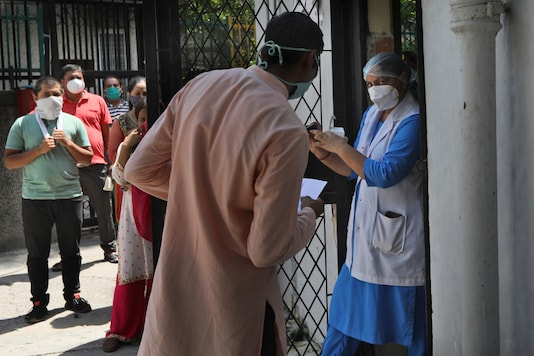 A health worker explains the working of an oximeter to an asymptomatic person who tested positive for Covid-19.  (AP Photo/Manish Swarup)