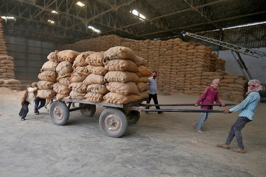 Labourers move a cart loaded with rice bags inside a food processing unit, which was reopened after weeks-long shutdown due to Covid-19. (File photo/Reuters)