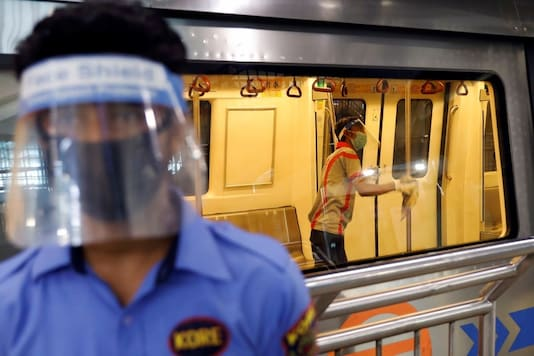 A worker wearing a face shield and mask cleans inside a train at a Delhi Metro station ahead of the restart of its operations, amidst the spread of coronavirus disease (COVID-19), in New Delhi, India, September 3, 2020. REUTERS/Adnan Abidi