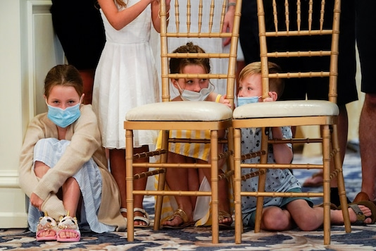 Children who had not been wearing protective facemasks wear masks just provided to them by the White House because of the coronavirus pandemic as they wait to watch US President Donald Trump hold a news conference at his golf resort in Bedminster, New Jersey, US. (Reuters)