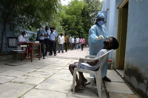 Residents queue up to register their names as a health worker collects a swab sample to test for coronavirus, in Hyderabad on Friday. (AFP)