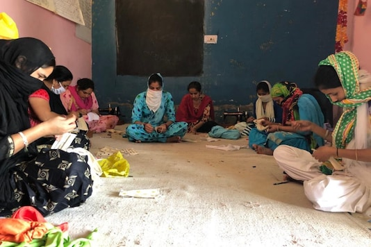 Women making phulkari face masks in Punjab.