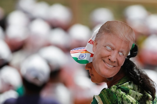 A woman wears a mask depicting U.S. President Donald Trump during the