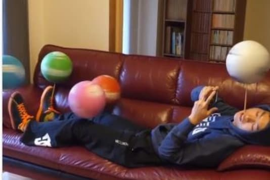 Screenshot of the video showing the man spinning five footballs at a time.