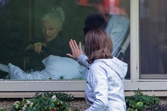 A woman visits her mother, 81, who tested positive for coronavirus at Life Care Center of Kirkland, the Seattle-area nursing home at the epicenter of one of the biggest coronavirus outbreaks in the United States. The pandemic, and the subsequent lockdowns imposed around the world left thousands of people longing for physical touch, for a hug, for love and for some semblance of what life used to be. (Credit: Reuters)