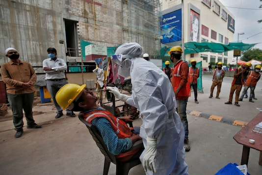 A healthcare worker wearing personal protective equipment (PPE) takes swab from a construction worker for a rapid antigen test at a construction site, amidst the coronavirus disease (COVID-19) outbreak, in Ahmedabad.