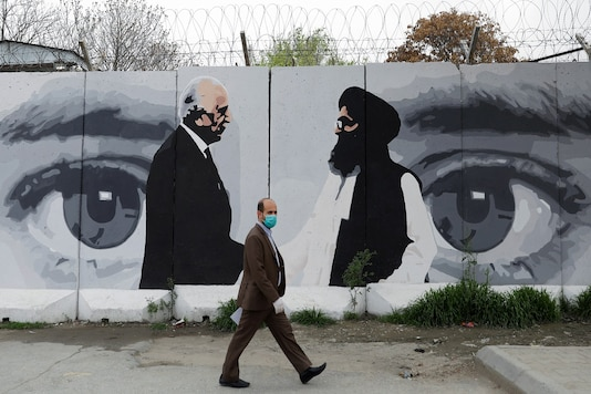 An Afghan man walks past a wall painted with photo of Zalmay Khalilzad, US envoy for peace in Afghanistan, and Mullah Abdul Ghani Baradar, the leader of the Taliban delegation, in Kabul. (File photo: Reuters)
