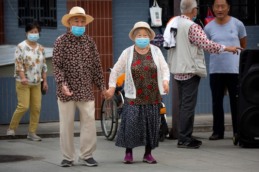 An elderly couple wearing face masks to protect against the coronavirus walks at a public park in Beijing,