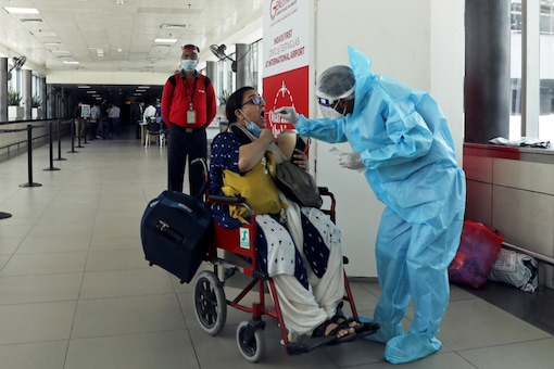 A health worker in personal protective equipment (PPE) collects a swab sample from a woman amidst the spread of the coronavirus disease (COVID-19) at Indira Gandhi International Airport, in New Delhi, India. REUTERS/Anushree Fadnavis