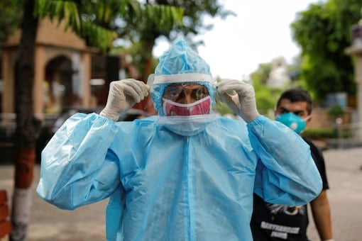 A relative wearing personal protective equipment (PPE) adjusts his protective face shield before the cremation of a man who died due to coronavirus disease (COVID-19), at a crematorium in New Delhi. (Reuters)